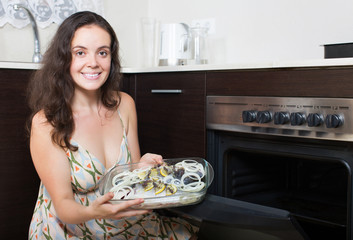 Woman putting fish in oven