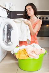 Unhappy  woman using washing machine