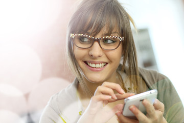 Young woman with eyeglasses websurfing on smartphone