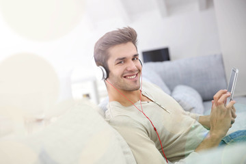 Young man with headphones watching movie on tablet