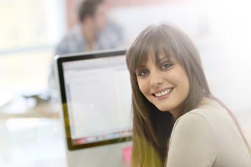 Student girl sitting in front of desktop computer