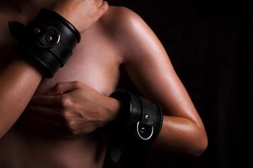 nackte Frau mit ledernen Armfesseln