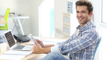 Young man in office working on digital tablet