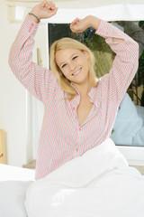 Twen in Pyjama streckt sich beim Aufwachen