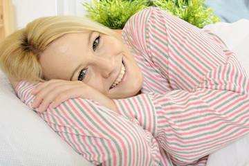 Twen in Pyjama beim Ausschlafen im Bett