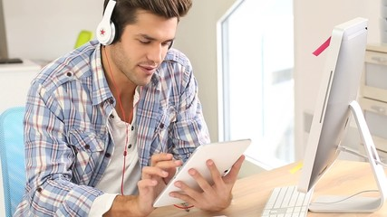 Student in office working on tablet with headphones on