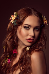 Fashion portrait of red-haired woman. Floral elements.