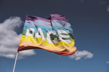 Pace, Peace Flag waving against blue sky