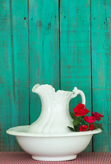 Antique water pitcher and basin with red flowers