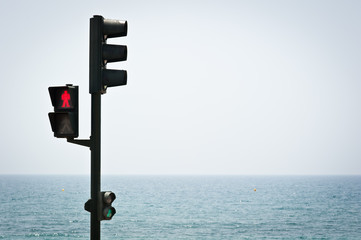 Pedestrian traffic light in red and the sea