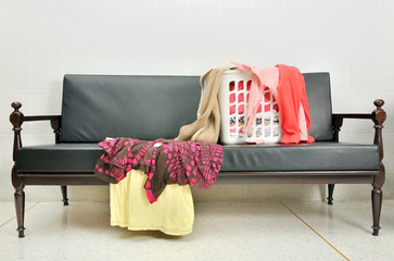 Messy clothes scattered in the basket on a sofa