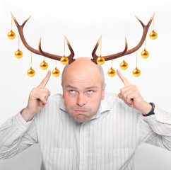 Funny man with reindeer antlers and christmas decoration.