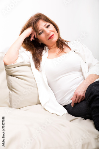 canvas print picture Schöne reife Frau auf dem Sofa