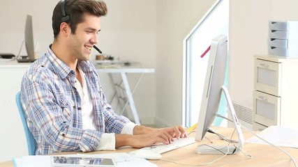 Young man in office working on desktop computer