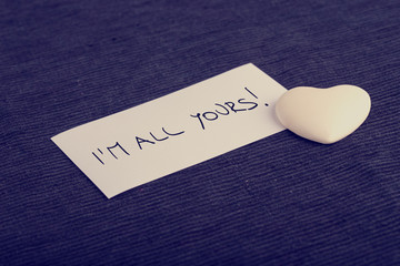 I'm all yours handwritten on a white card with a cream colored h