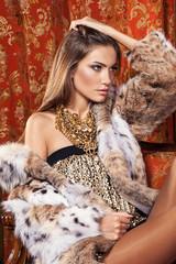 Fashion model posing in a fur coat in luxury interior.
