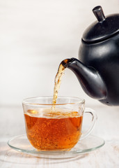 Cup of tea with pouring tea and black teapot