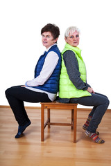 Two women sitting back to back on the chair