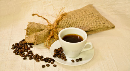 Cup of coffee with sack of roasted beans on white table-cloth