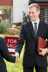 Estate agent shaking hand of client