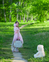 Girl in a pink dress with a suitcase walking along the forest