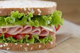 Ham sandwich on a cutting board.