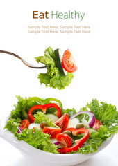 Vegetable salad in a white bowl and on fork  isolated on white
