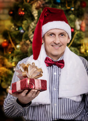 Portrait of a young man in Santa cap. Santa Claus with gifts in