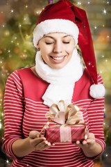 girl in a cap of Santa Claus with gifts in his hands