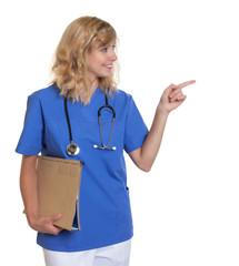 Krankenhwester mit blonden Haaren zeigt zur Seite