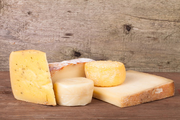Various types of cheese on a wooden background