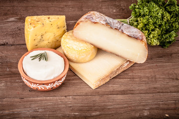Various types of cheese on a wooden background with parsley.Tint