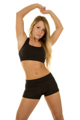 woman fintess black bra and shorts facing arms over head