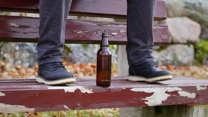 Beer bottle at a man's legs on the bench
