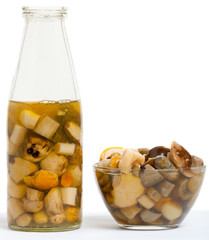 pickled mushrooms in a glass bottle and glass bowl