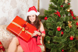 smiling lass wearing Christmas hat with big present box poster