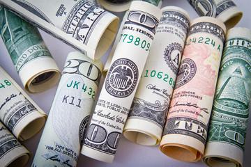 Банкноты доллары скрученные в трубочки лежат кучей