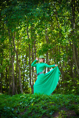 Beautiful girl in green dress in the forest