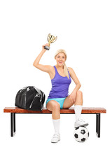 Female soccer player holding a trophy