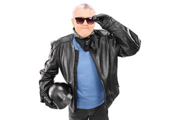 Cool mature motorcyclist holding a helmet