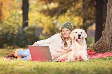 Woman enjoying a picnic with her dog in park