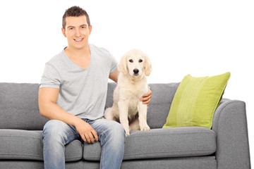Young guy sitting on a sofa with a cute puppy