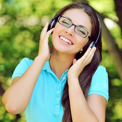 Beautiful young woman with headphones outdoors. Enjoying music