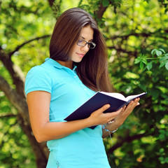 Young beautiful girl reading book in a park