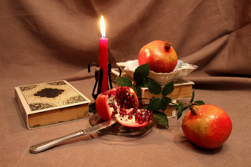 Still life with pomegranates and candle.