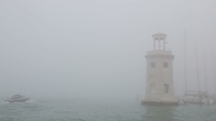 Lighthouse and motor boat in fog