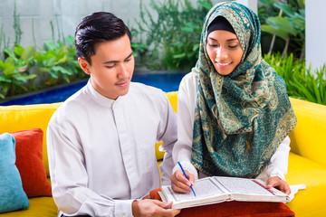 Asian Muslim couple reading together Koran or Quran