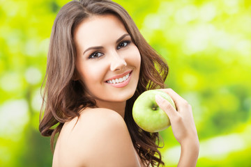 Young woman eating apple, outdoors