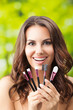 Smiling woman with make up tools, outdoors