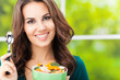 Smiling woman with salad, outdoor